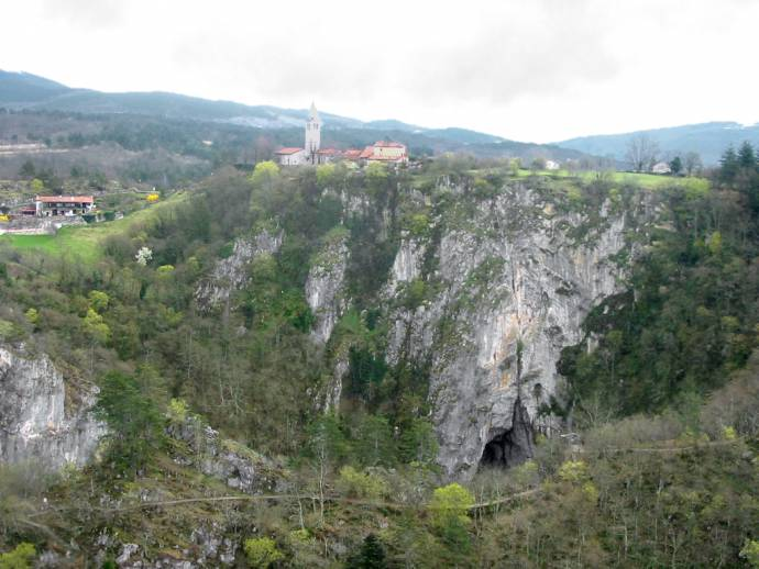 Village Skocjan, Divača, Slovenia. River Reka; resurges twice from under the Karst rock formations. In front below: View into first of 2 huge collapsed parts of cave Skocjanske jame (Mala Dolina).