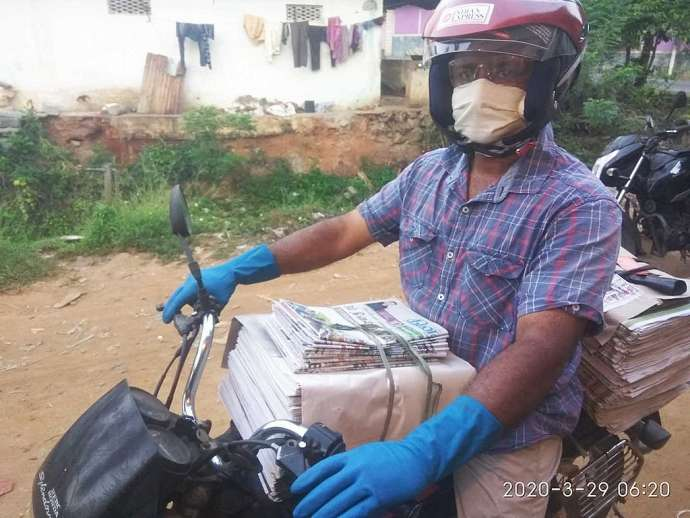 A civic-minded newspaper vendor in Tamil Nadu, India, wearing safety gloves, mask and safety screen