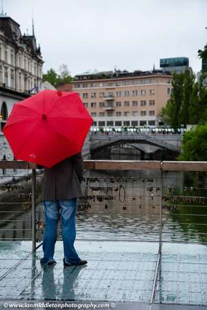Man holding a red umbrella and standing on The Butchers' Bridge looking over the Ljubljanica river towards the Trznica (market) Triple Bridge on a rainy day in Ljubljana, Slovenia. The wire fence on the bridge is covered with padlocks put there by locals and tourists. All this region was designed by Slovenia's most celebrated architect, Jože Plečnik.