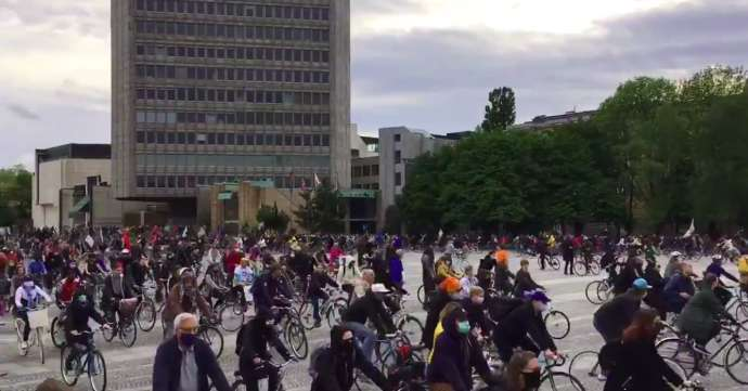 Protesters cycling around Trg Republike / Republic Square, in front of Parliament (off screen, to the right)